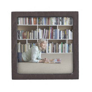 Older woman reading by bookshelves jewelry box