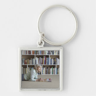 Older woman reading by bookshelves keychain