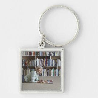 Older woman reading by bookshelves keychain