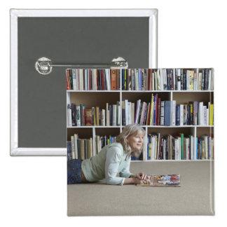 Older woman reading by bookshelves pinback button
