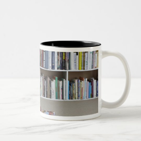 Older woman reading by bookshelves Two-Tone coffee mug