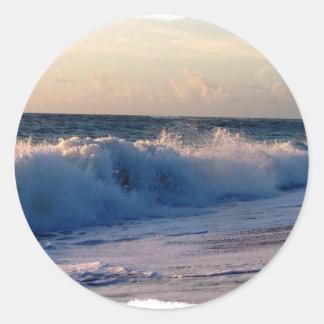 Ondas de fractura decididas en una playa de la pegatina redonda