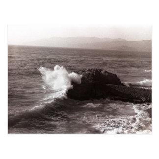 Ondas del mar que se estrellan contra roca postal