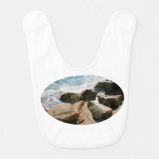 ondas en rocas en imagen de la orilla de la playa baberos para bebé