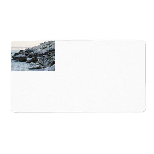 Ondas que golpean rocas grandes en la orilla etiqueta de envío