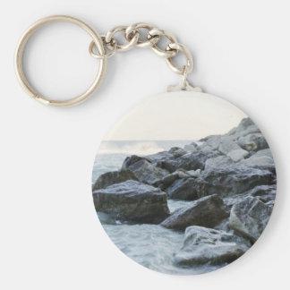 Ondas que golpean rocas grandes en la orilla llavero redondo tipo pin