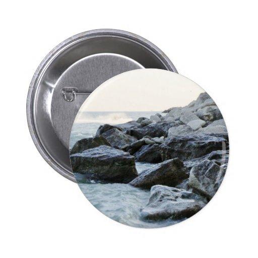 Ondas que golpean rocas grandes en la orilla pin redondo 5 cm