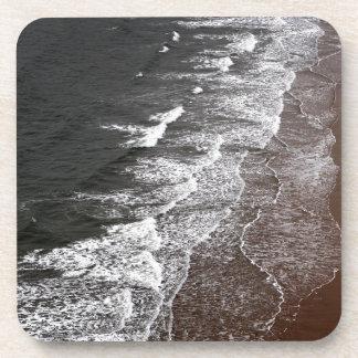 Ondas que se rompen en una playa arenosa posavasos de bebida