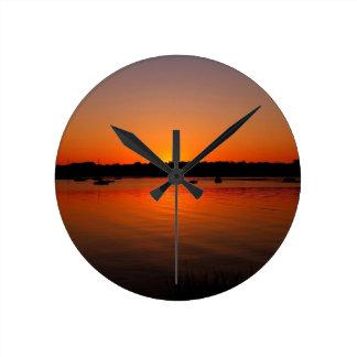 Ondulaciones de la puesta del sol reflejadas relojes de pared