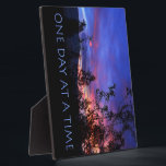 """One Day at a Time Spring Sunrise Plaque<br><div class=""""desc"""">The recovery slogan ONE DAY AT A TIME over a spring landscape at sunrise. Vibrant pink,  yellow,  purple,  orange and blue shines through plum tree and pine silhouettes. Nice gift!</div>"""