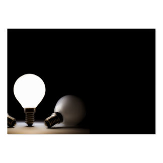 One light bulb shining in a dark space large business card