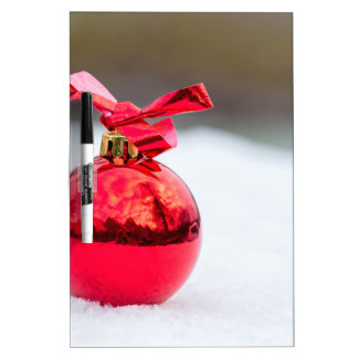 One shiny red christmas ball outside in snow dry erase board