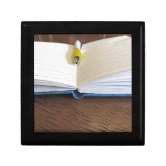 Opened blank lined notebook with pen jewelry box