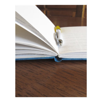 Opened blank lined notebook with pen letterhead