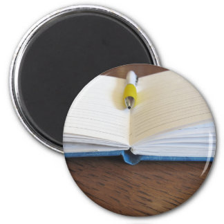 Opened blank lined notebook with pen magnet