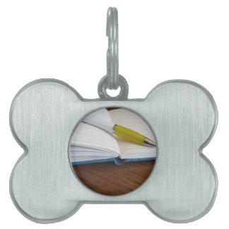 Opened blank lined notebook with pen pet name tag