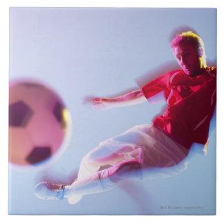 Opinión borrosa el jugador de fútbol que golpea la azulejo cuadrado grande