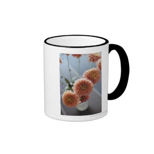Opinión de alto ángulo de flores en un florero tazas de café