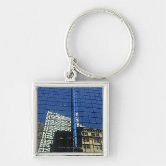 Opinión de ángulo bajo de la reflexión de edificio llavero cuadrado plateado