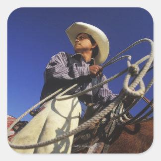 Opinión de ángulo bajo un vaquero que monta un pegatina cuadrada
