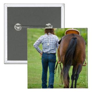 Opinión trasera la mujer que lleva su caballo pin cuadrada 5 cm