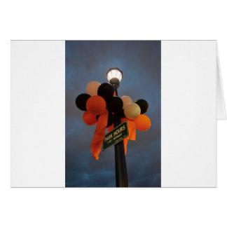 Orange and Black Balloons Adorn a Park Sign Card