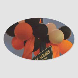 Orange and Black Balloons Adorn a Park Sign Oval Sticker