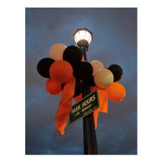 Orange and Black Balloons Adorn a Park Sign Postcard