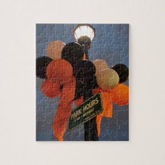 Orange and Black Balloons Adorn a Park Sign Puzzle