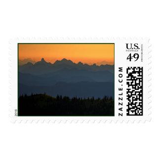 Orange and blue sunset with crashing ocean wave postage stamp