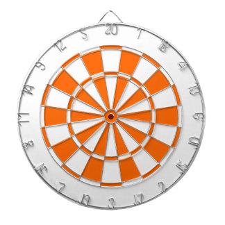 orange and white dartboard with darts