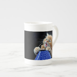 Orange Cat Cub Playing and Biting Blue Tea Cup