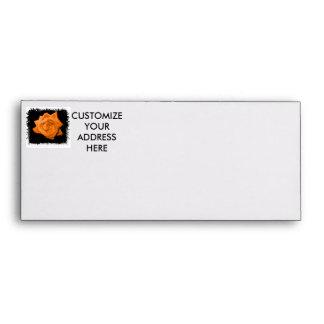 Orange colored rose against black back envelope
