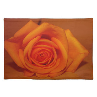 Orange colorized rose against orange background cloth placemat