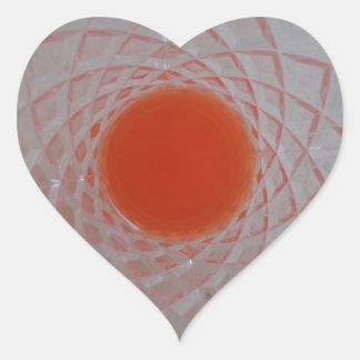 Orange drink inside a crystal glass heart sticker