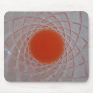 Orange drink inside a crystal glass mouse pad