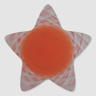 Orange drink inside a crystal glass star sticker