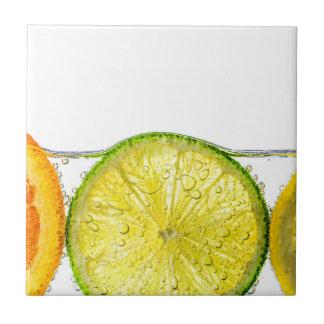Orange lemon and lime slices in water tile