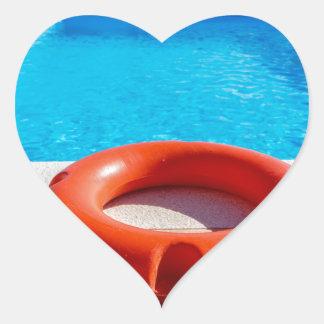 Orange life buoy at blue swimming pool heart sticker