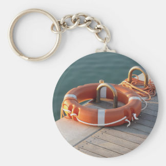 Orange life buoy on wooden pier in the harbor basic round button keychain