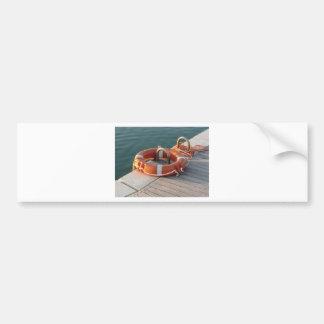Orange life buoy on wooden pier in the harbor bumper sticker