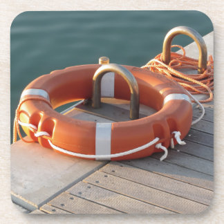 Orange life buoy on wooden pier in the harbor drink coasters