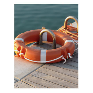 Orange life buoy on wooden pier in the harbor postcard