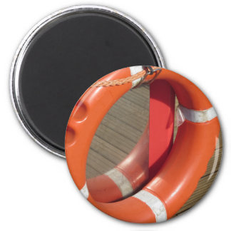 Orange lifebuoy on wooden pier in the harbor 2 inch round magnet