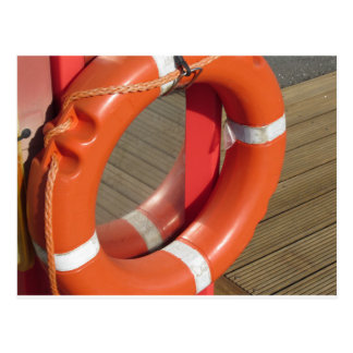 Orange lifebuoy on wooden pier in the harbor postcard