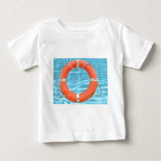 Orange lifebuoy over swimming pool water backgroun baby T-Shirt