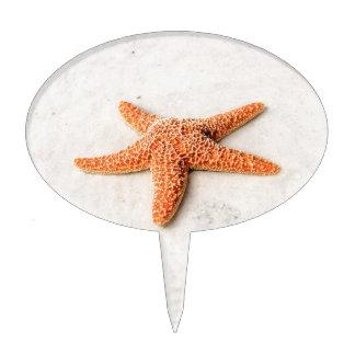 Orange starfish on a white sandy beach cake topper