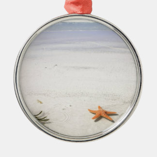 Orange starfish on a white sandy beach metal ornament