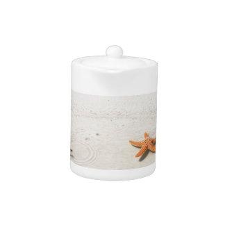 Orange starfish on a white sandy beach teapot