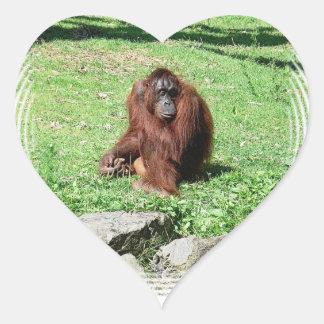 Orangután cabelludo rojo marrón que se sienta en pegatina en forma de corazón